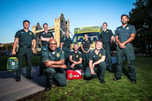 Image shows London Ambulance Service paramedics posed in front of Tower Bridge on a sunny day in London.