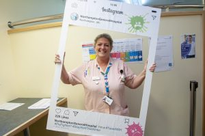 Clinical staff member at Northampton General hospital holding up selfie frame with flu messaging