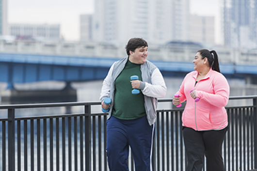 An overweight man and woman exercising together in a city along the waterfront. They are jogging or power walking, looking at each other, talking. They are carrying handweights. The man is in his 20s, mixed Hispanic and Caucasian. His Hispanic friend is in her 30s.