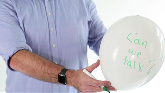 Man holding a ballon with the words can we talk written on it