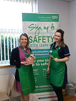 Two nurses standing in front of a Sign up to Safety banner