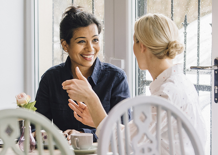 Women are sitting at a table in a cafe, socialising over tea.