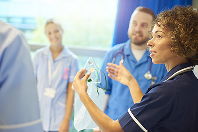 A senior staff nurse instructs a group of young male and female nurses about the oxygen breathing apparatus on the ward.
