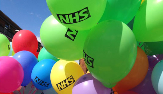 Image of a bunch of balloons with the NHS logo on.