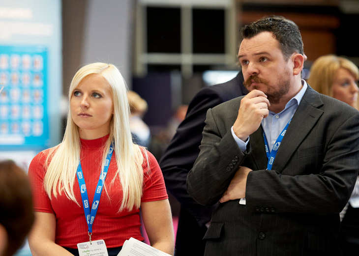 Two people listen to a speaker at Expo