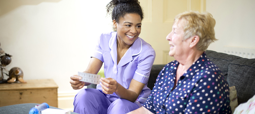 A care worker visits a patient at home