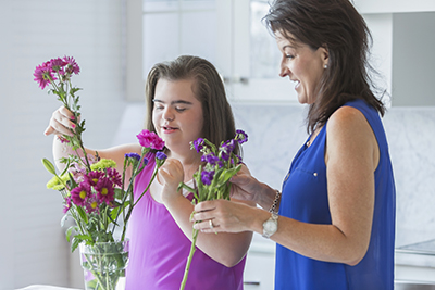 A teenage girl with learning disabilities arranges some flowers