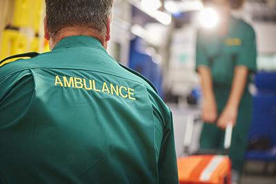 An ambulance crew pulling a stretcher