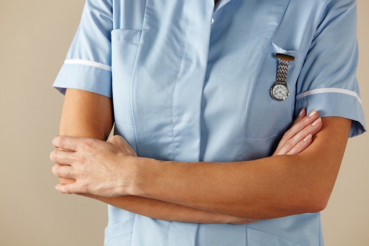 A nurse stands with her arms folded