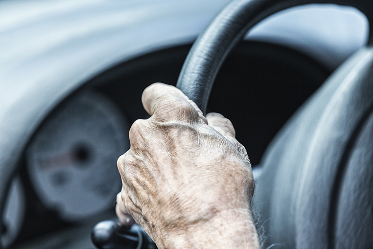 A close up of a hand on a steering wheel