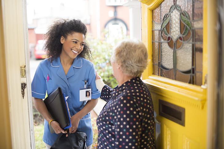 A nurse visits a patient at home