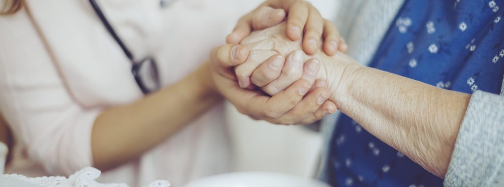 Healthcare professional and patient holding hands