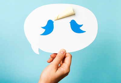 A person holding up the Twitter logo