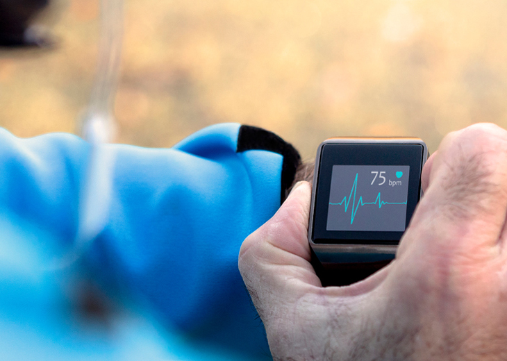 A man checks his heart rate on a wrist monitor