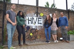 A group of young people standing by The Hive sign