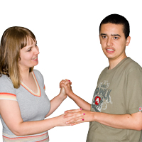 A women and a young man opposite each other and holding hands, the women is smiling at the young man
