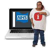 "A women pointing to herself, she is wearing a jumper with an 'i"" on it. She is stood in front of a computer screen with a picture of a flag with ""NHS"" written on it."