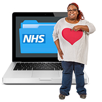 Lady pointing to herself wearing a jumper with a big heart, standing in front of a monitor with an image of an NHS folder