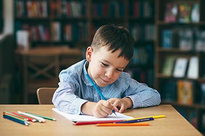 Young boy sat at a desk doing homework.