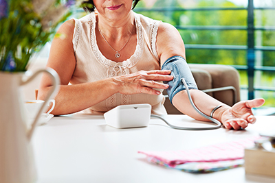 Mature woman sitting at the table at home and checking her blood presure.