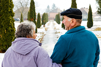 Elderly couple walking in the snow.