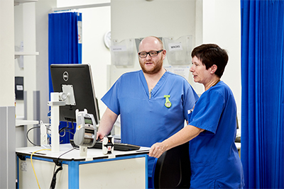 Male and female nurses talking while looking at a computer screen.