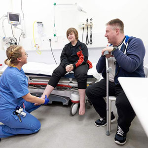 A young person with two healhtcare professionals looking at their feet