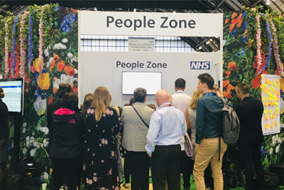 Group of people stood in front of a stand with the title People Zone.