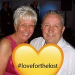 A couple posing for a photo with a yellow lover hart, within which the word #loveforthelost