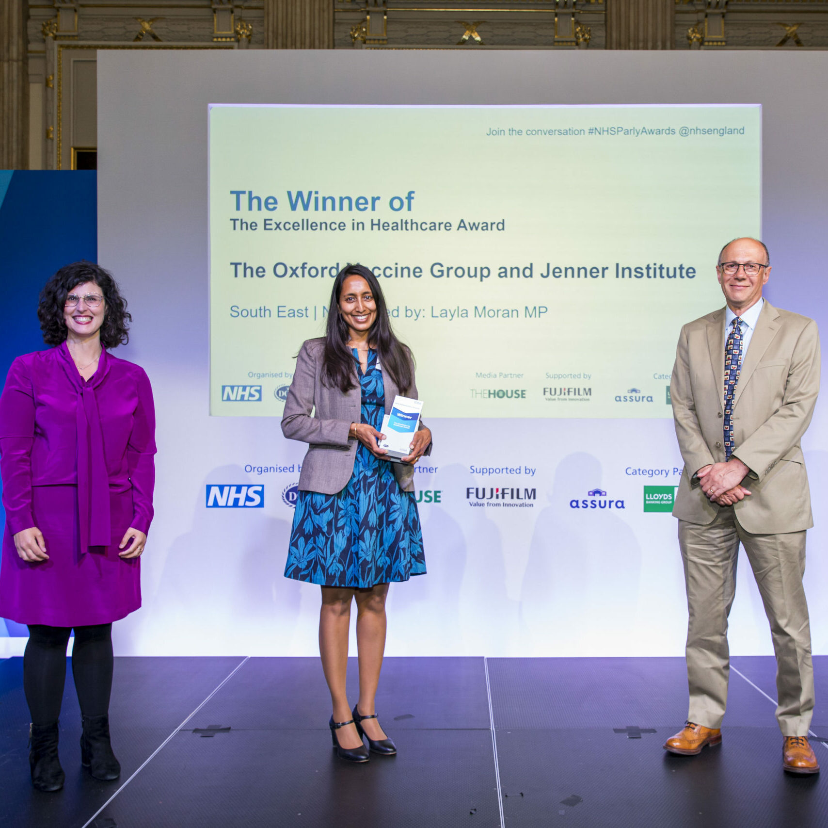 Three people are stood on the stage with a member of The Oxford Vaccine Group and the Jenner Institute receiving their Parliamentary NHS Award