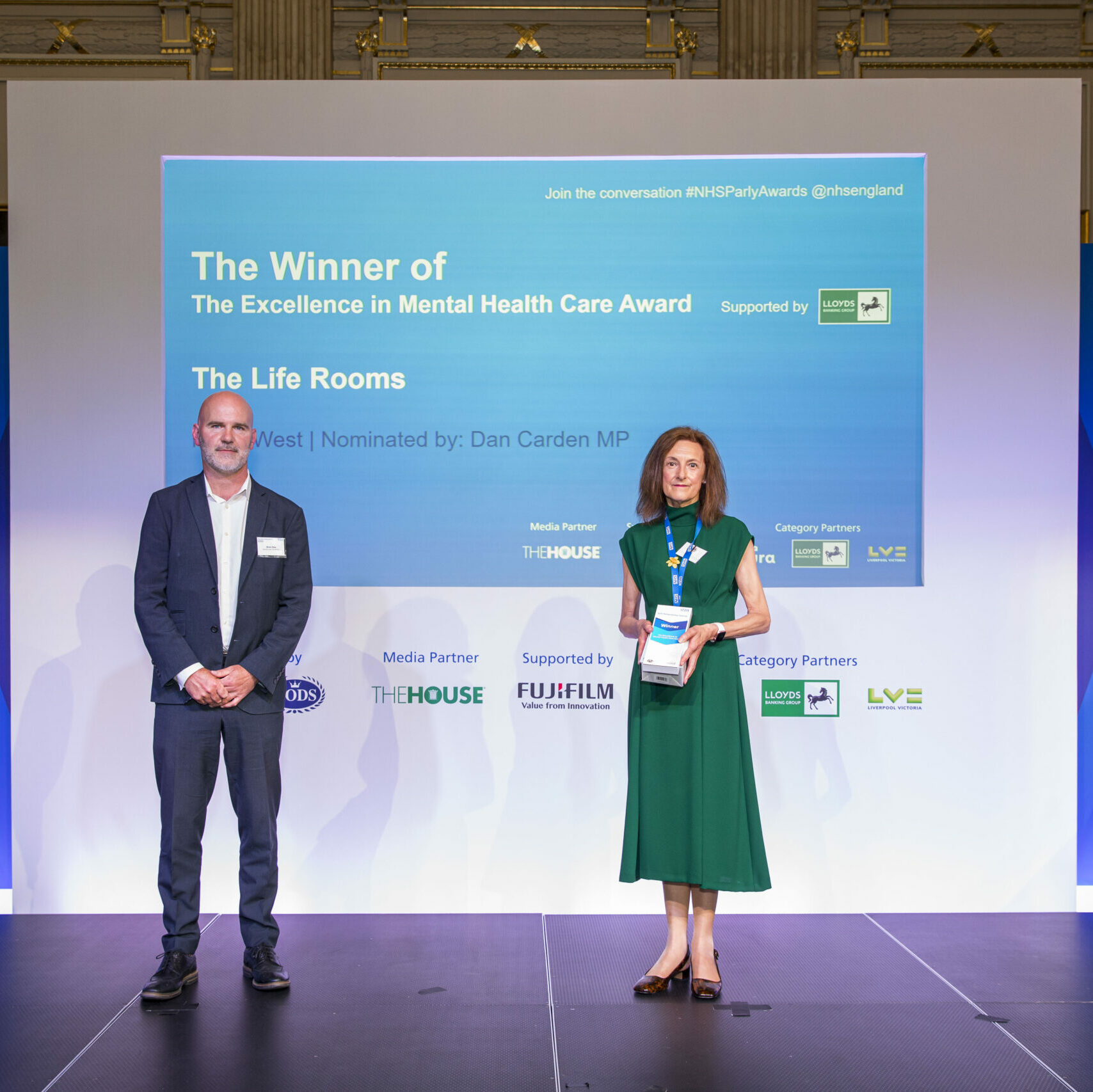 Two people are stood on the stage from The Life Rooms, Mersey Care receiving their Parliamentary NHS Award