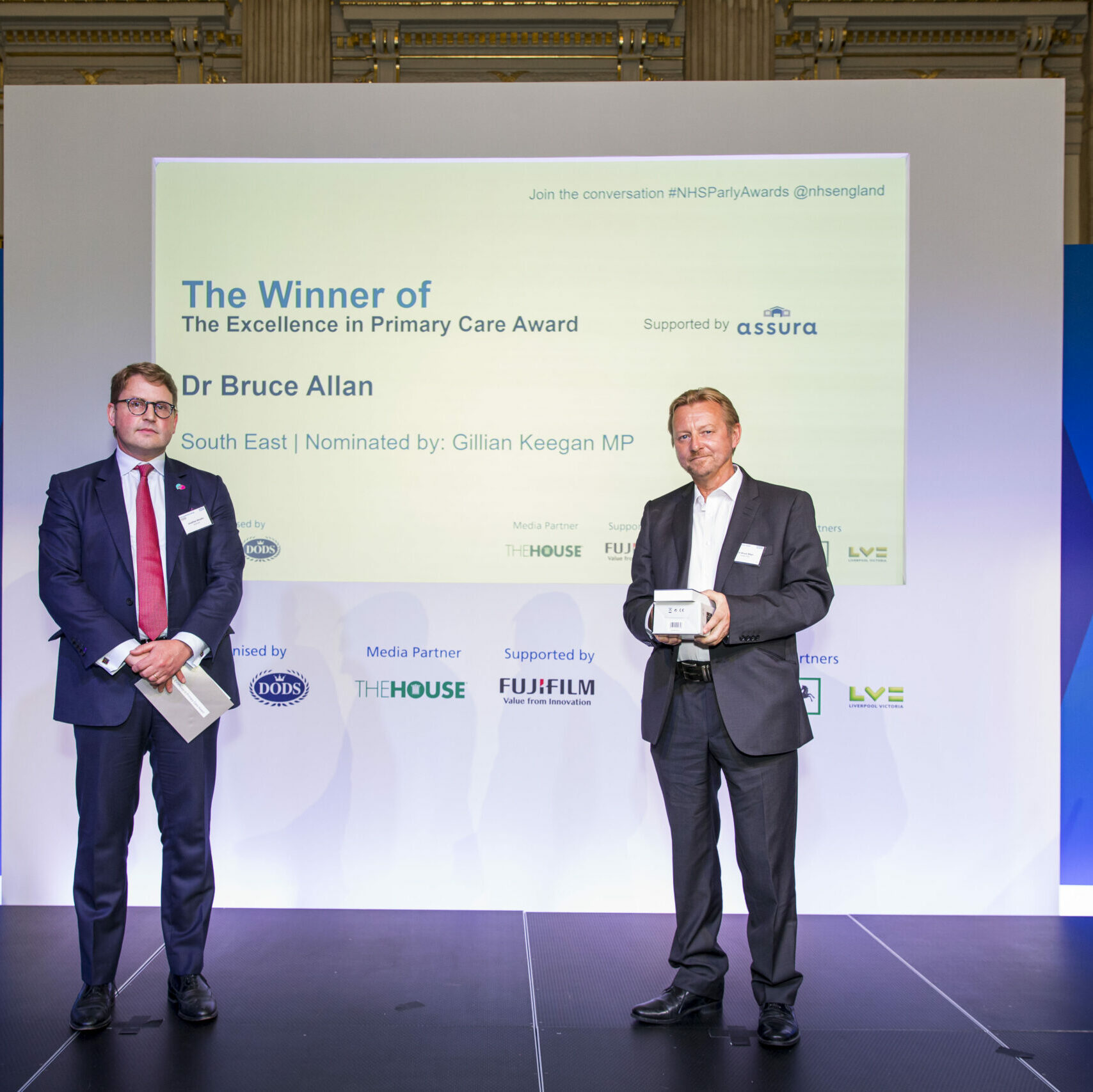 Dr Bruce Allan is stood on a stage and receives The Excellence in Primary Care Award