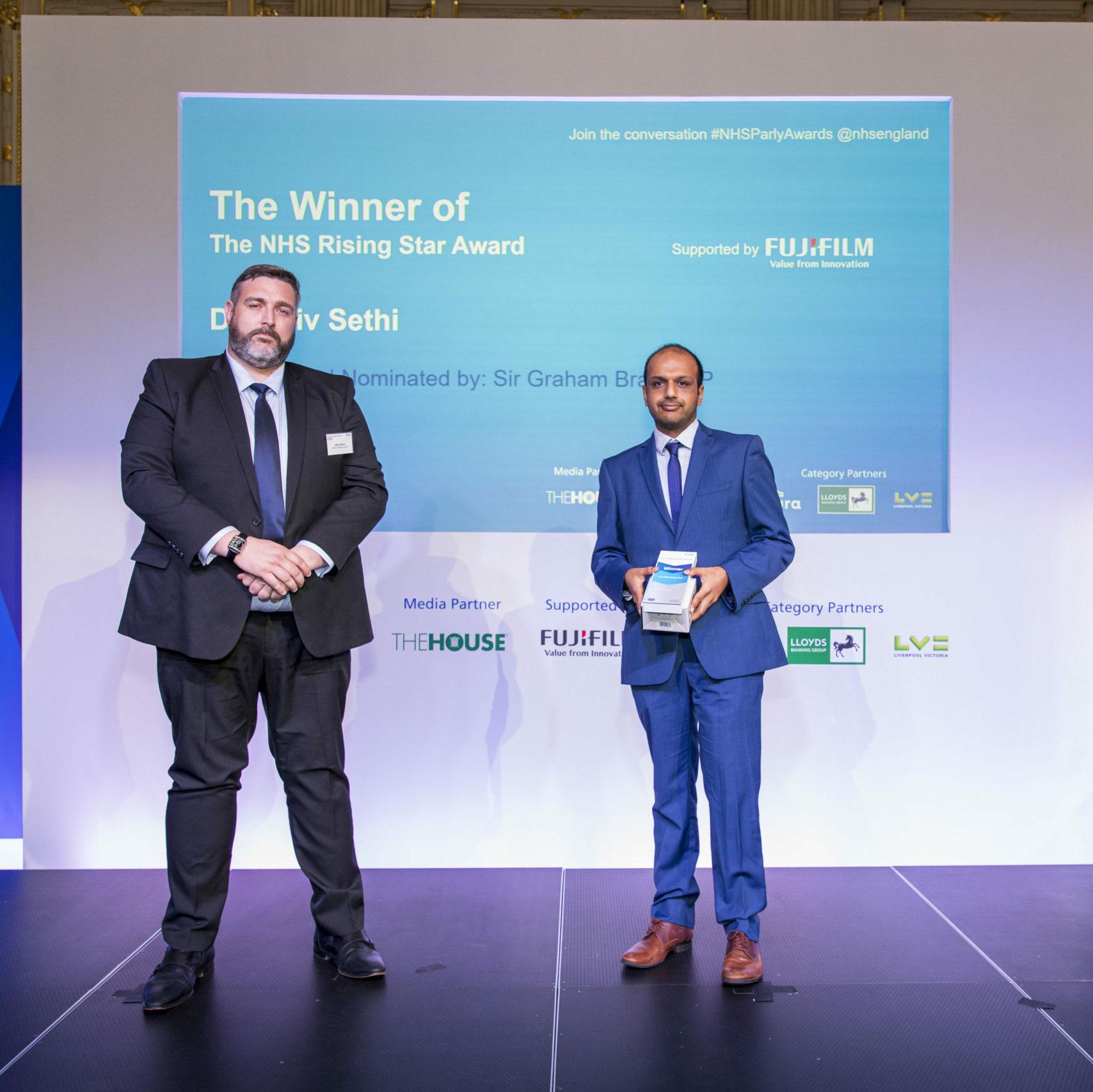 Rajiv Sethi is stood on stage receiving The NHS Rising Star award