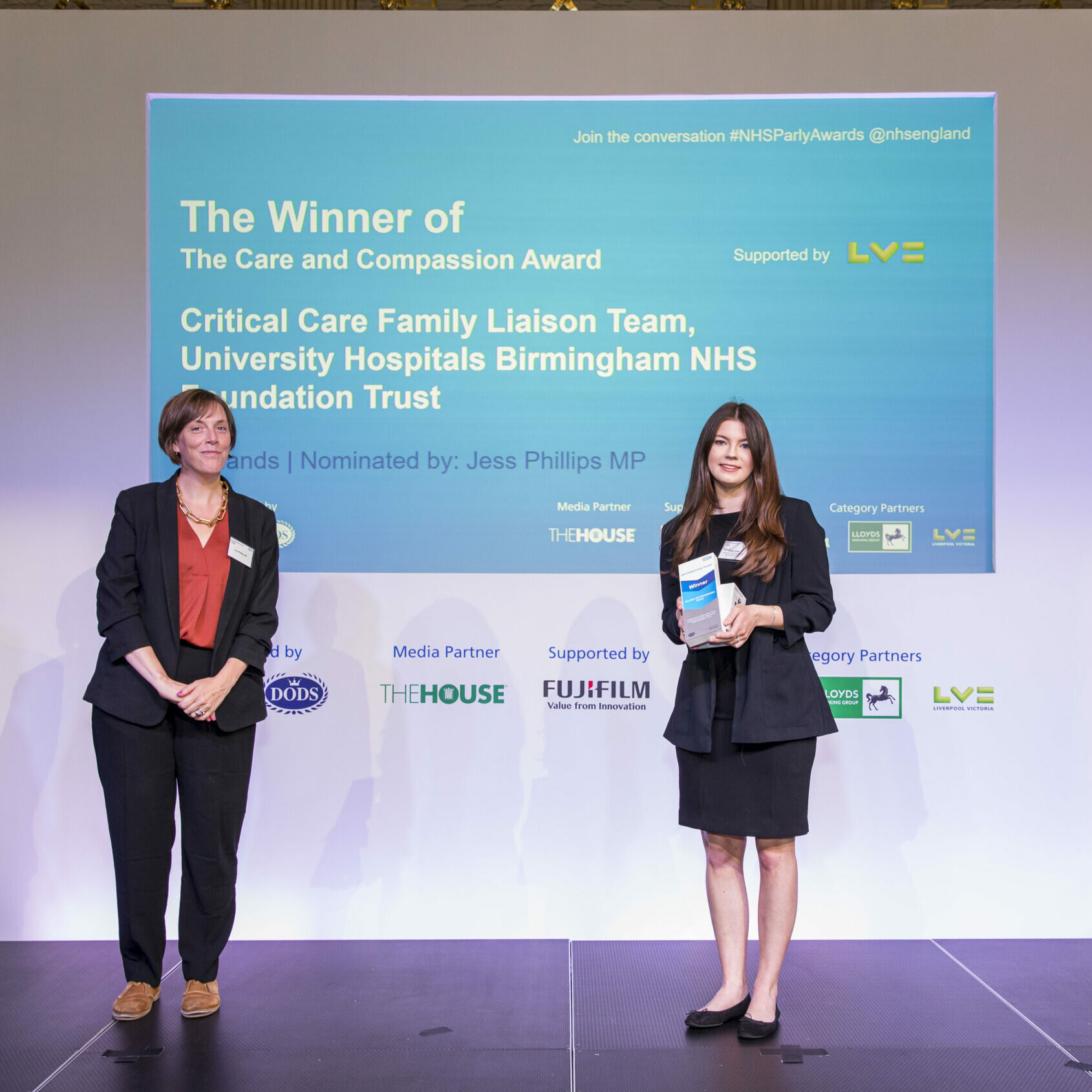 Two people are stood on a stage with a member of the Critical Care Liaison Team receiving their award