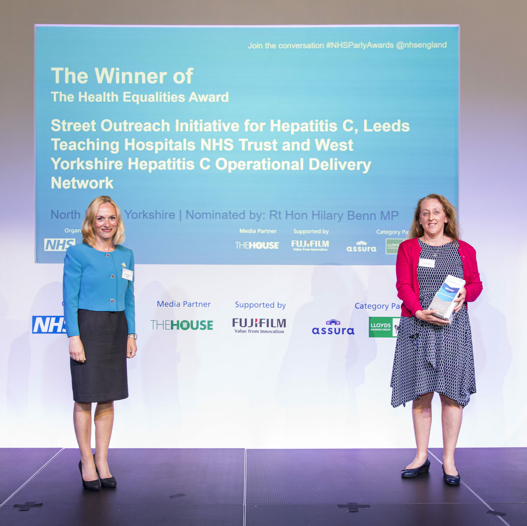 A member of the Street Outreach Initiative for Hepatitus C team is stood on stage receiving The Health Equalities Award