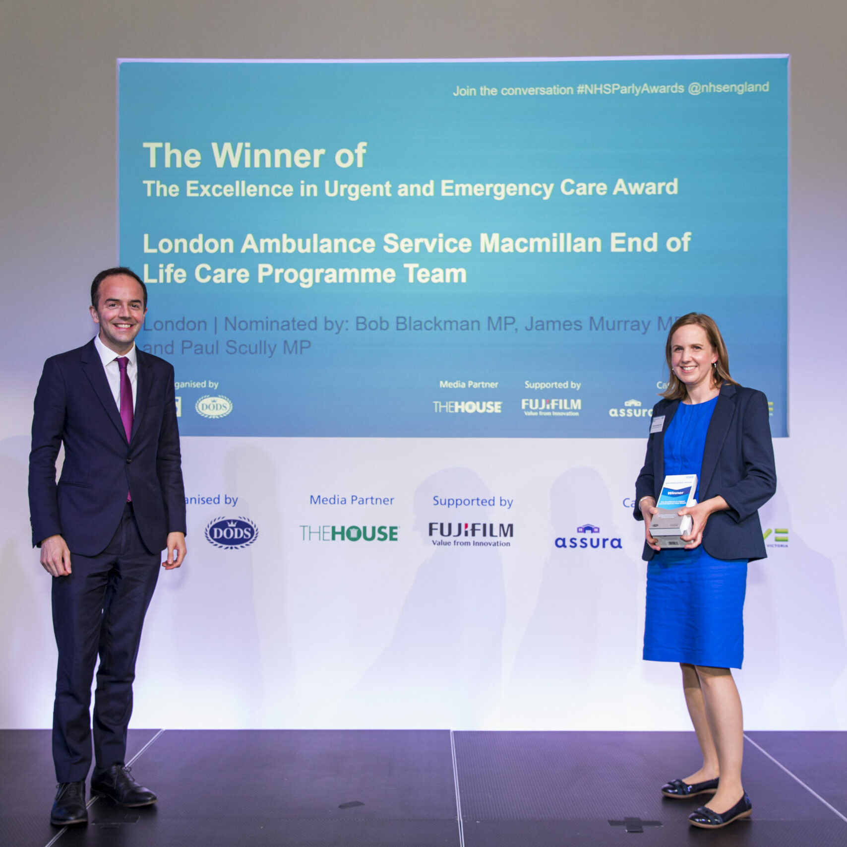 A member of the London Ambulance Service Macmillan End of Life Care Programme Team is stood on stage receiving their Excellence in Urgent and Emergency Care Award